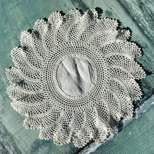 Beautiful circular vintage crochet doily with a starburst design.