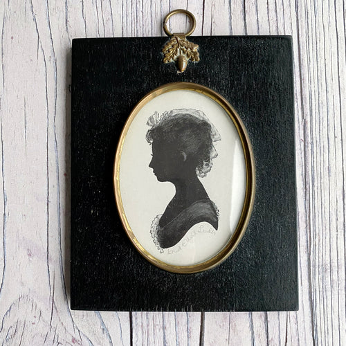 Silhouette female portrait picture framed. Black, white and gold.