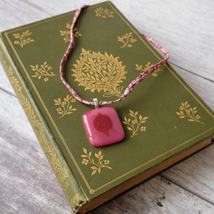 Glass pendant featuring a vintage book design on Liberty print fabric cord