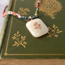 Load image into Gallery viewer, Glass pendant featuring a vintage book design on Liberty print fabric cord