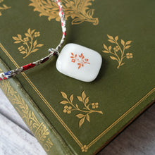 Load image into Gallery viewer, SALE Glass pendant featuring a vintage book design on Liberty print fabric cord