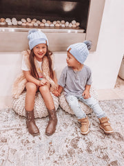 brother and sister wearing matching winter pom pom beanies, cubs and co