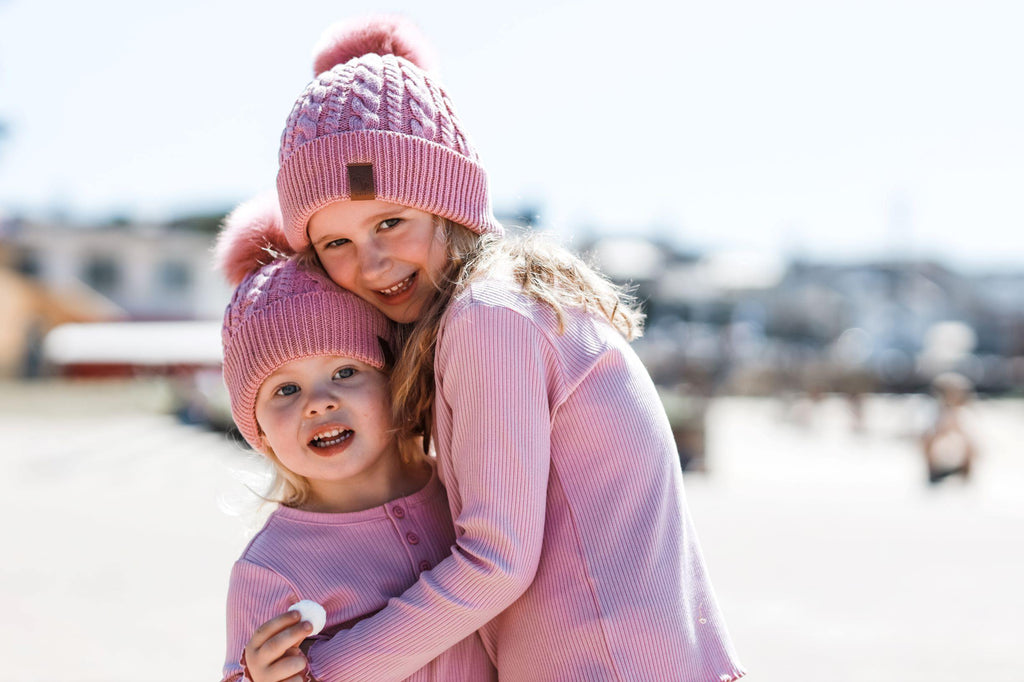 Sisters wearing pink winter cotton beanies with pom pom. Cubs & Co. Australia.