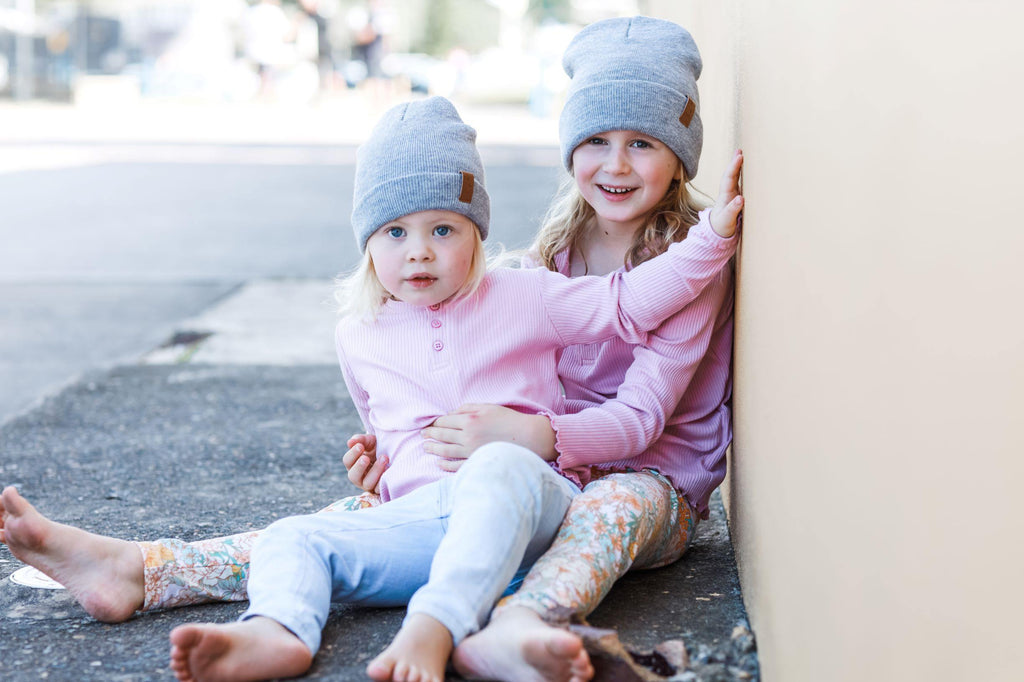 Girls wearing matching grey winter beanies. Cubs and Co. Australia