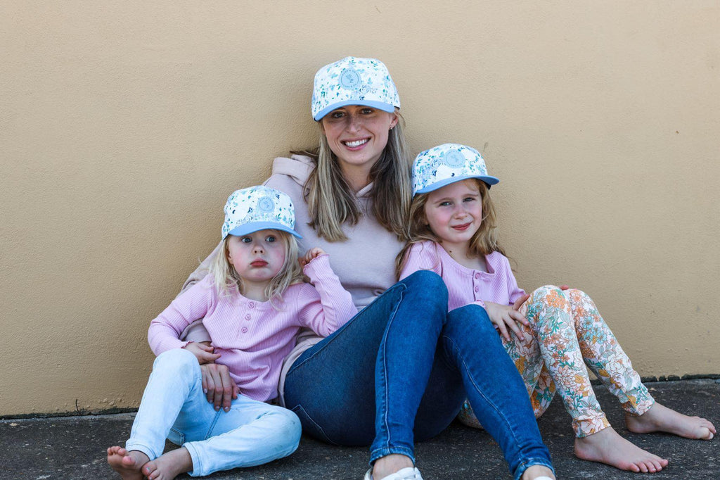 Matching mum and daughters wearing blue floral baseball snapback caps. Cubs & Co. Australia.