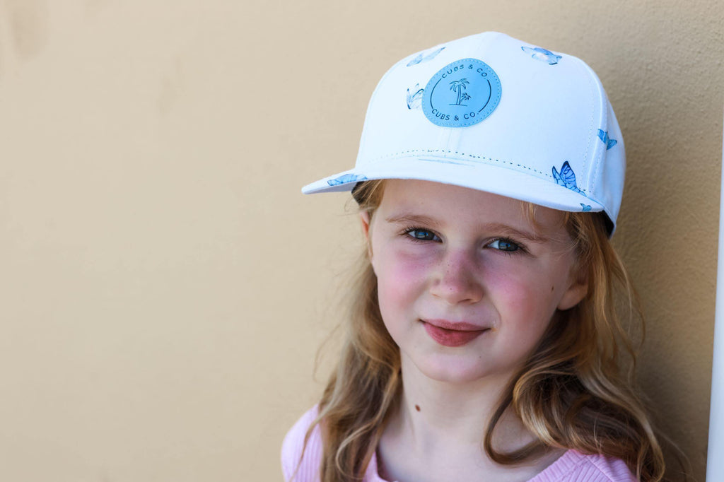 Girl wearing a blue butterfly snapback baseball cap. Cubs & Co. Australia