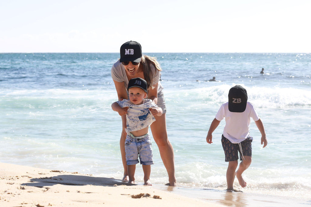 Mum and sons wearing matching personalised black baseball caps with their initials. Cubs & Co. Australia.