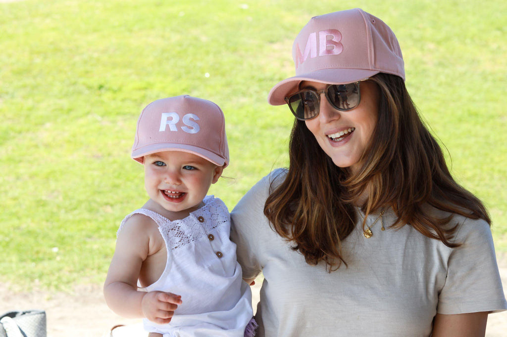 Mum and daughter wearing matching personalised pink baseball caps with their initials. Cubs & Co. Australia.