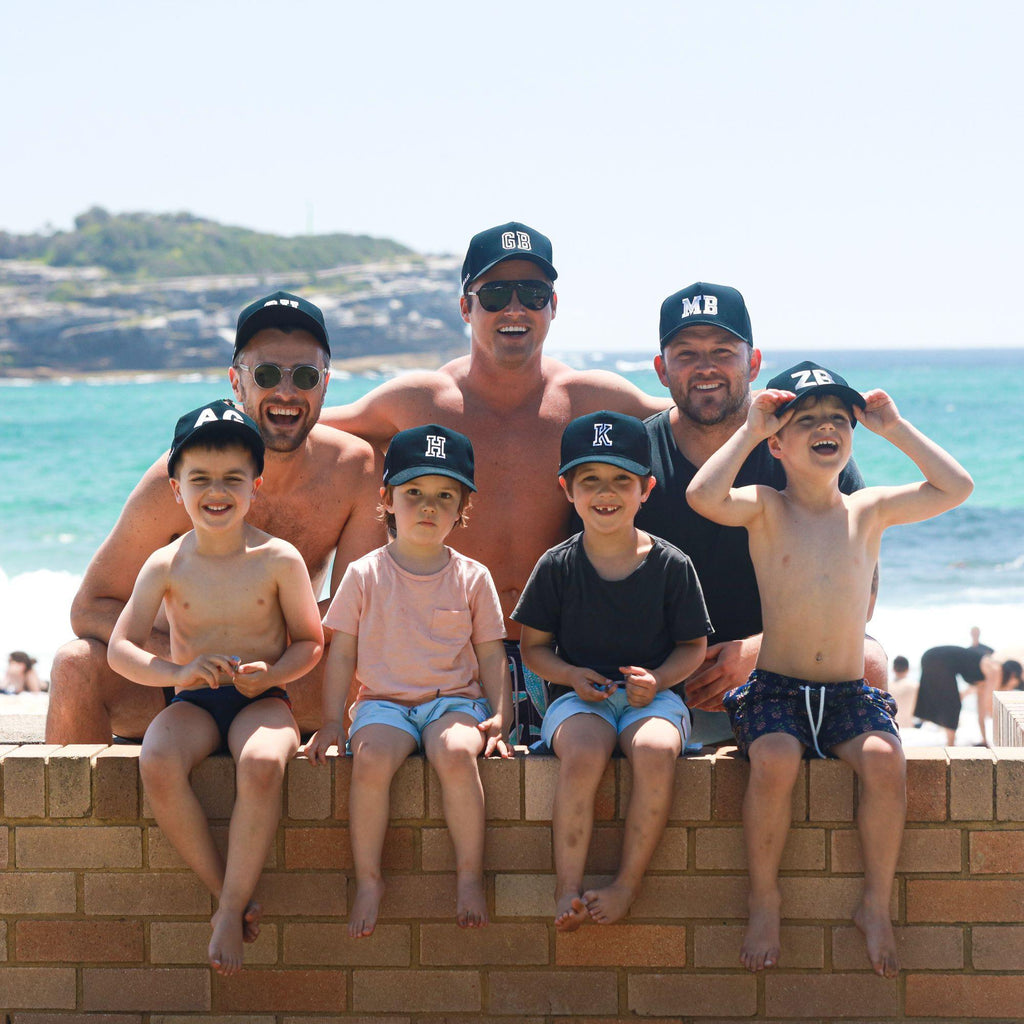 Boys and men wearing matching personalised black baseball caps with their initials. Cubs & Co. Australia.