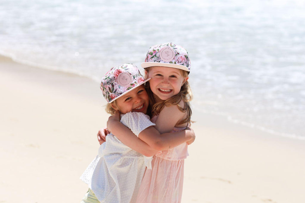Girls wearing matching pink floral snapback hats. Cubs & Co. Australia.