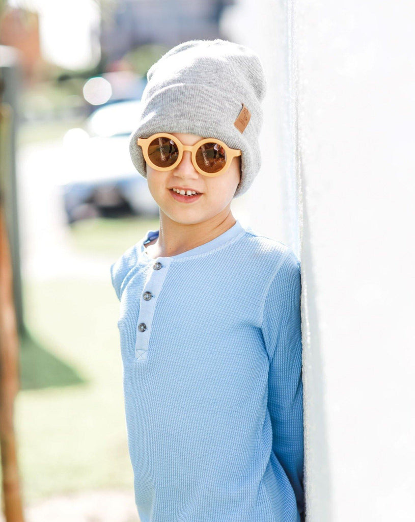 Boy wearing kids yellow butterscotch sunglasses with UV protection. Cubs & Co. Australia