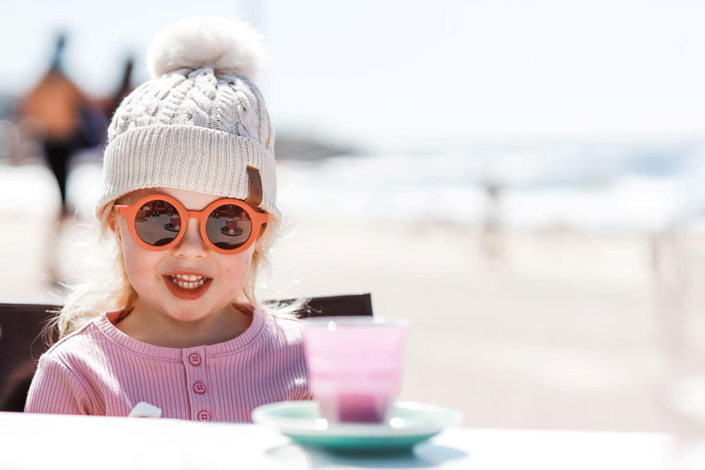 Girl wearing cream pom pom beanie and kids orange terracotta sunglasses with UV protection. Cubs & Co. Australia