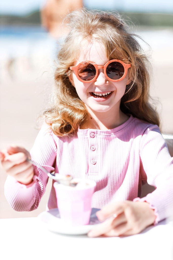 Girl wearing kids orange terracotta sunglasses with UV protection. Cubs & Co. Australia