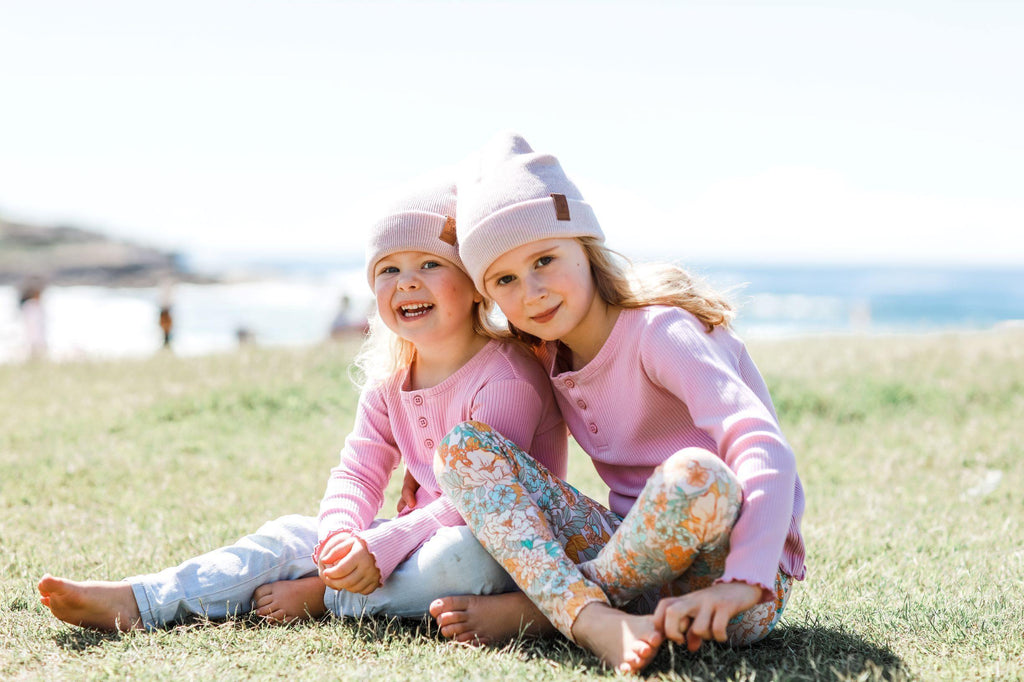 Sisters wearing matching pink winter beanies. Cubs and Co. Australia