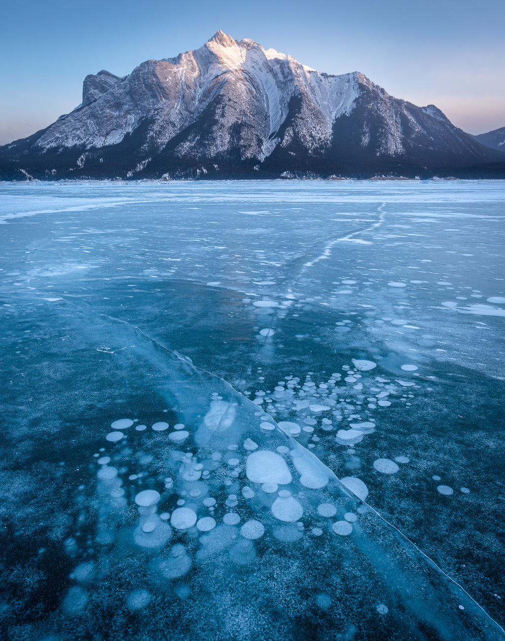 Methane bubbles frozen in Abraham Lake and Mount Michener during sunset