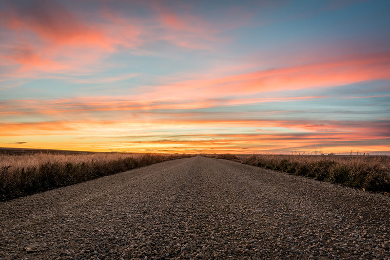Gravel road in rural Alberta at sunset with colourful skies