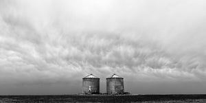 Grain bins in severe weather, Alberta prairies, black and white landscape photography