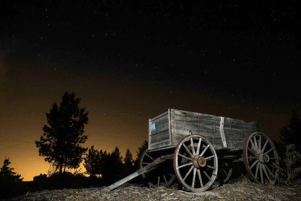 Retired old wagon, agriculture relic underneath Calgary city lights