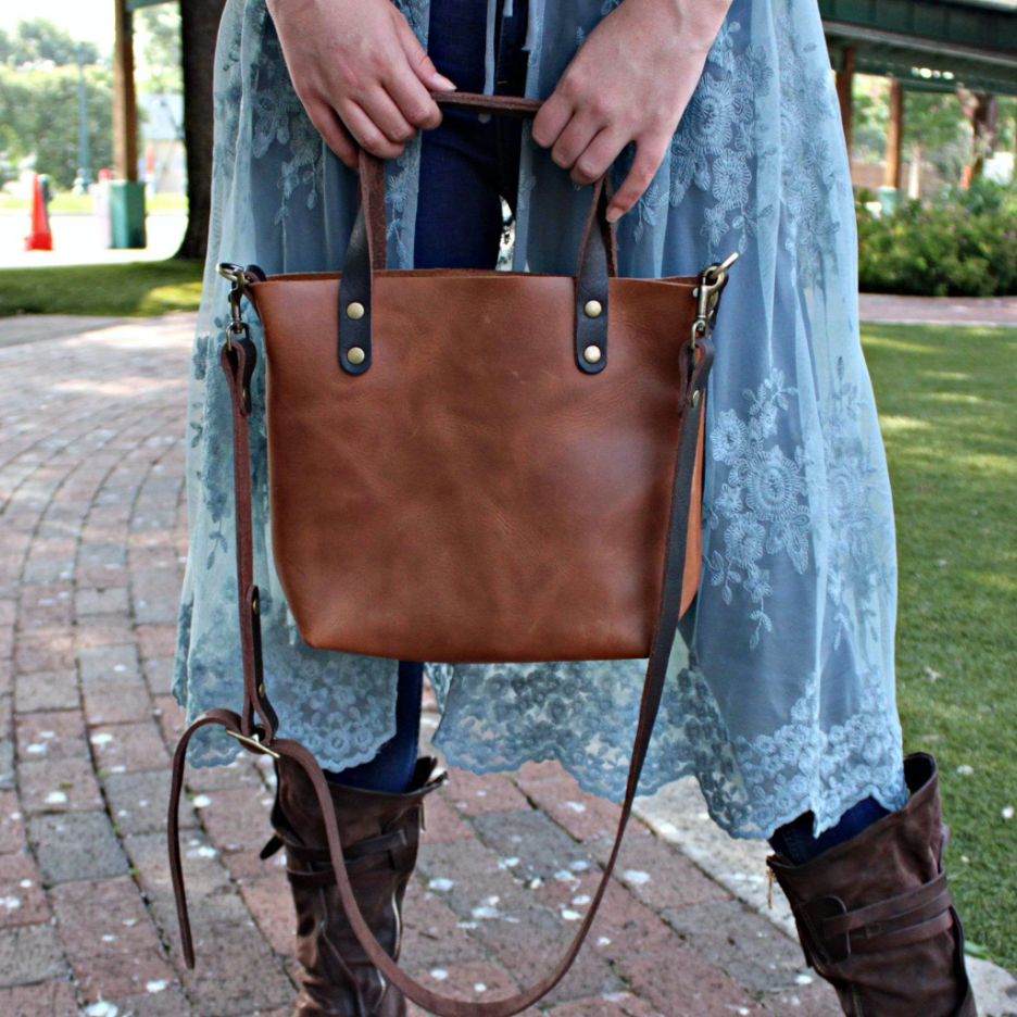 A model on a brick sidewalk holding her full-grain crossbody tote bag by Kerry Noël. In fall fashion, the bag matches her riding boots and cute blue cardigan perfectly.