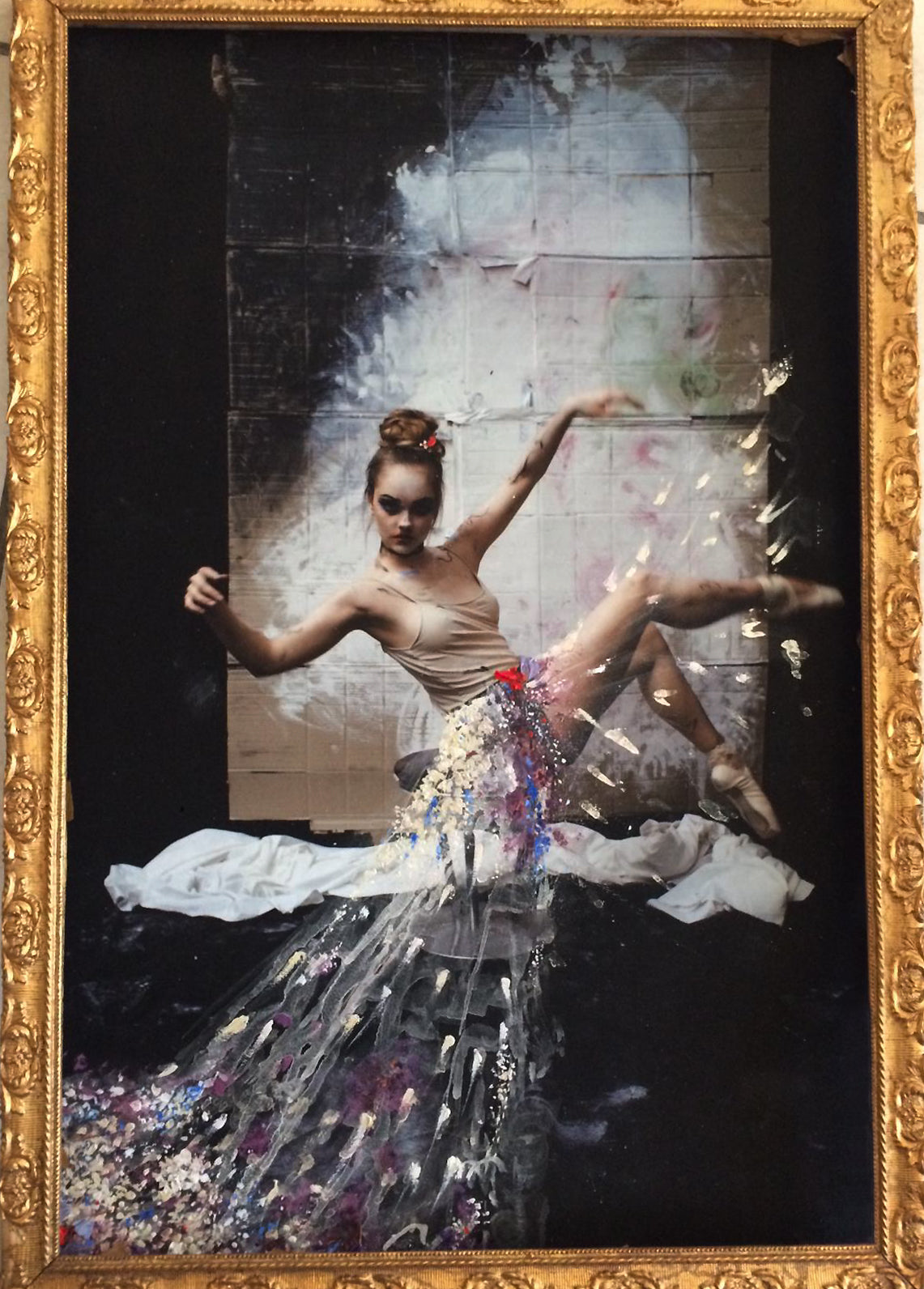 Gold framed piece of a ballerina kicking her legs in pointe shoes. She has a painted skirt of iridescent flowers that blurs as she kicks.