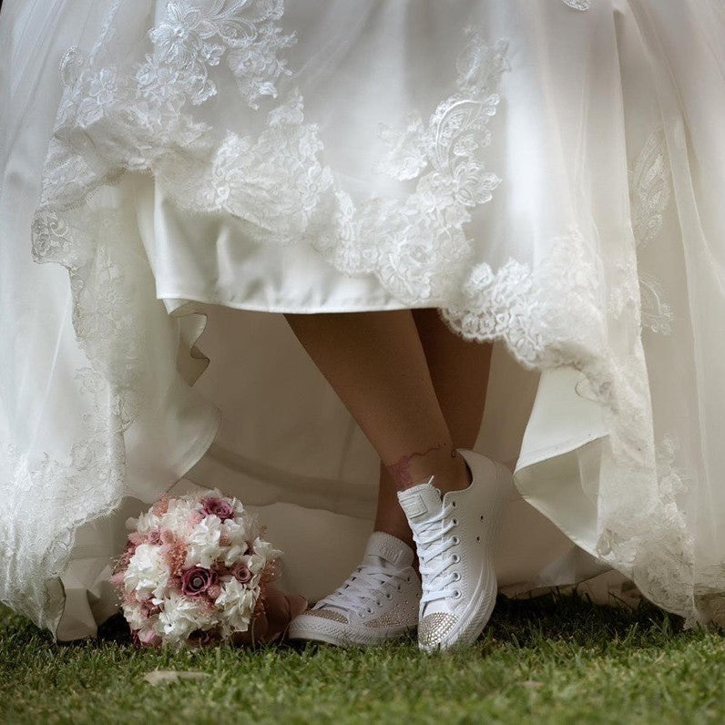Bride lifting dress to show Swarovski wedding converse trainers