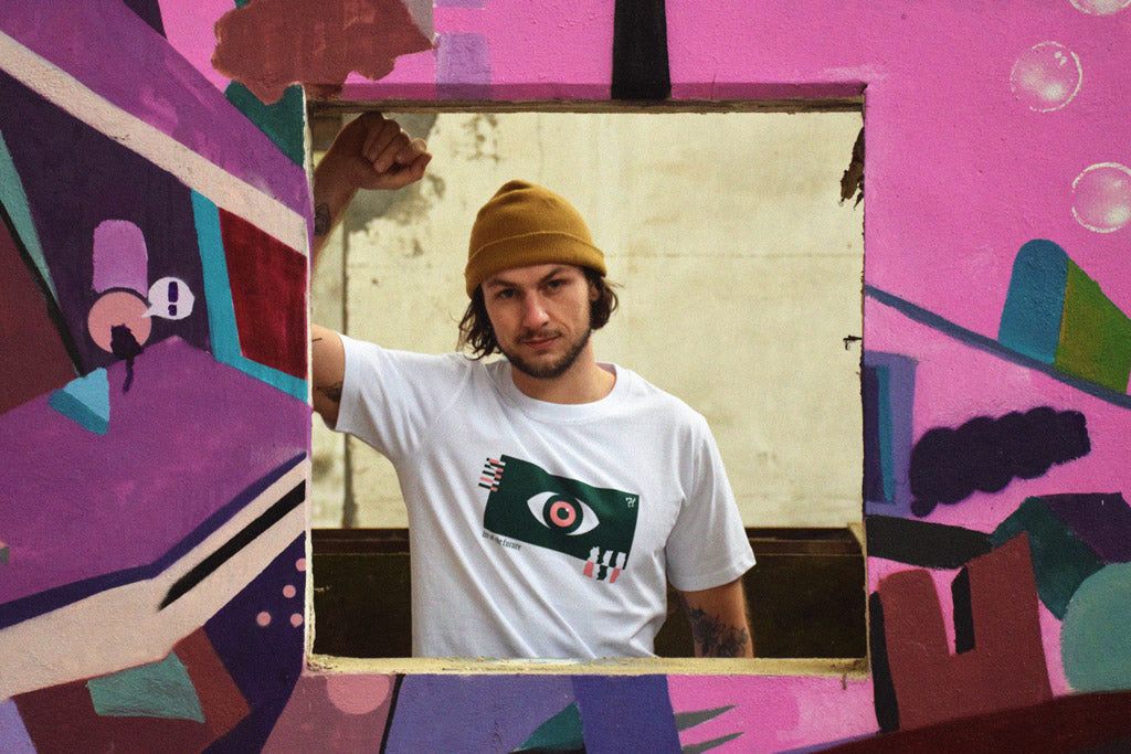 Model wearing white t-shirt with green and pink graphic behind graffiti wall