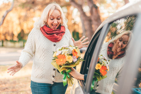 Blond hair excited middle-aged lady looking surprised at the flower bouquet given by her man who sits in a car - spring