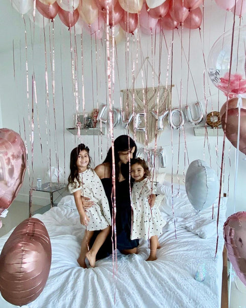woman hugging two kids on a bed decorated with balloons