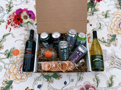 A red wine and white wine bottle on either side of a box with 6 beers and stemless wine glasses against a floral background