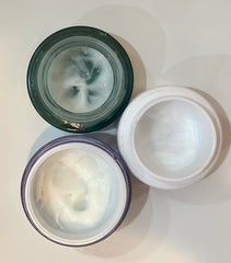 3 moisturizer jars opened from aerial view