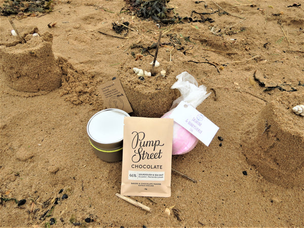 The Mini Bliss Box contents, body butter, bath bomb and mini Pump Street chocolate on a beach background with sand castle