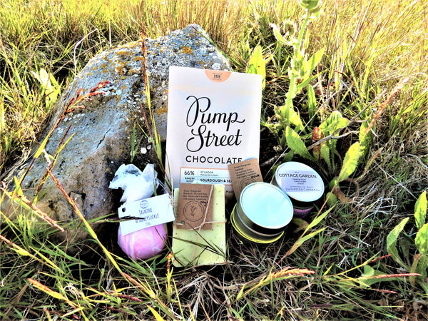 Bliss Box contents of soap, body butter, bath bomb, candle and Pump street chocolate in a wild grass setting