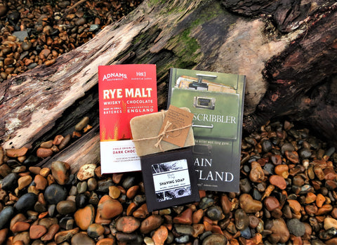 The Bloke Box contents - The Scribbler Book, Shaving Soap, Adnams chocolate and natural shampoo/soap bar - on a clay and pebble background