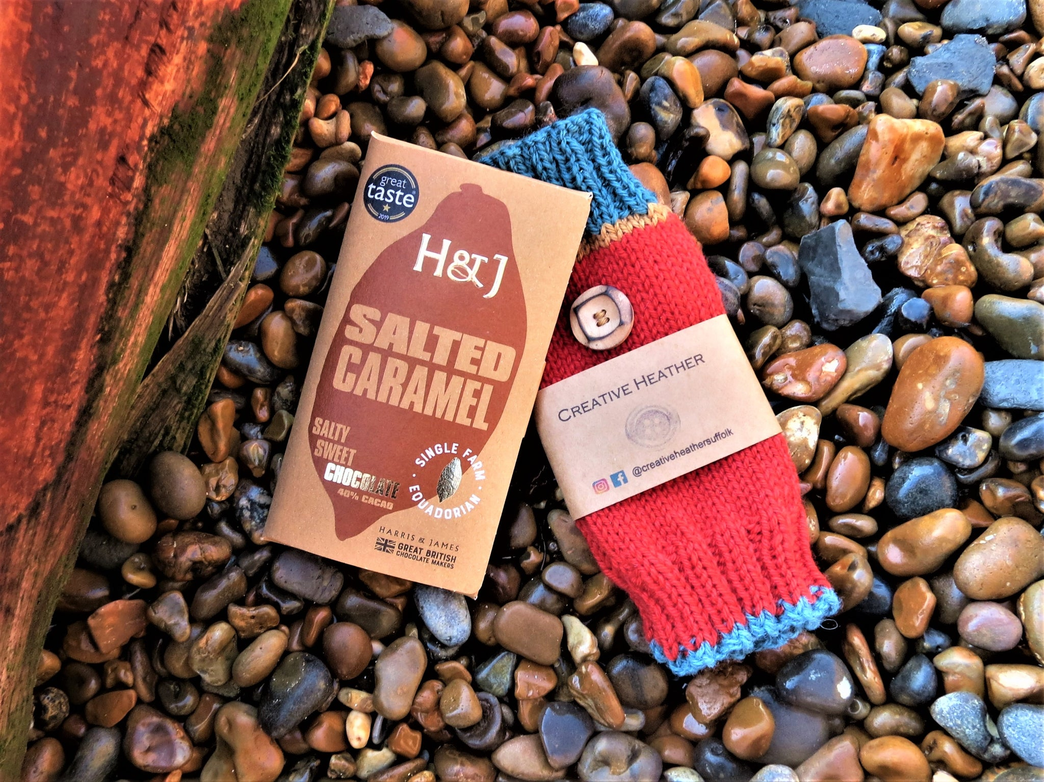 The Cosy Couple Box contents - wrist warmers and H&J chocolate - on a beach setting