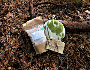 The Mini Bath Box contents, Body sponge, Bath salts and Natural soap, shown on a forest floor setting