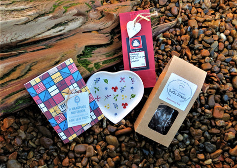 The Take 5 Box contents, healthy vegan bites, breakfast long leaf tea, note book, pocket hug and wildflower heart plate on a beach background