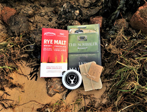 The Bearded Bloke Box contents - The Scribbler Book, The Bearded Stagg beard balm, Adnams chocolate and natural shampoo/soap bar - on a beach background