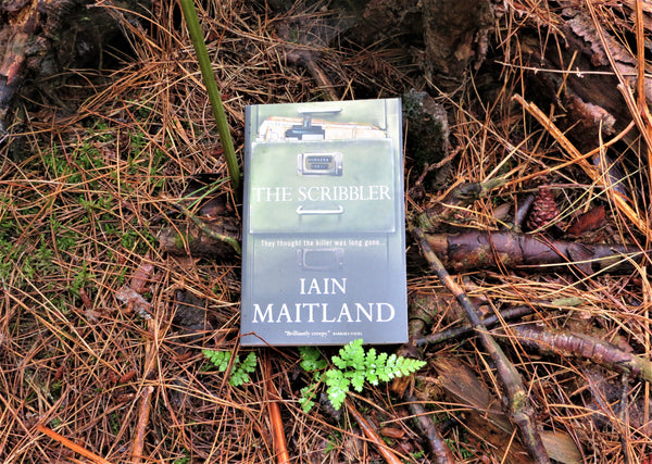 The Scribbler book by Suffolk author Iain Maitland on a forest floor background