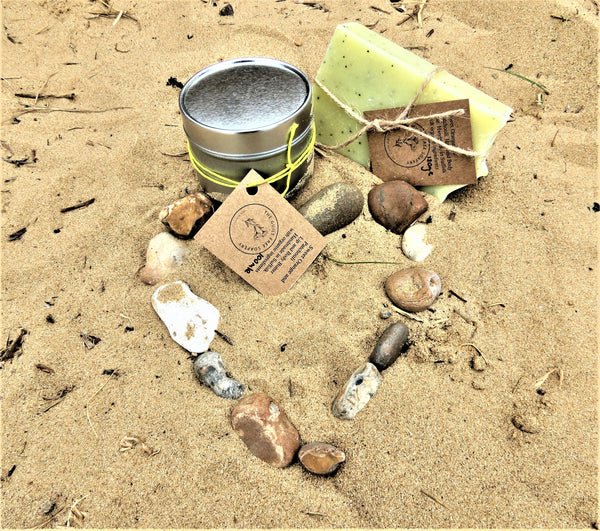 Guilt FreeSoapery Body Butter and Shampoo/Soap Bar on the beach next to a heart made with pebbles