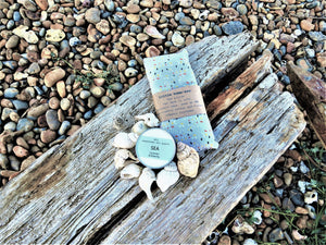 The Perfect Pair Box contents, organic eye pillow and Sea candle on a driftwood background