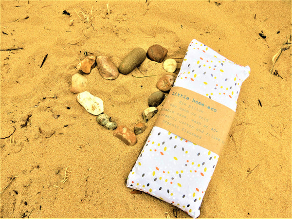 Organic eye pillow on a beach background with a heart of pebbles