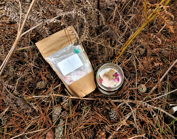 Bath salts by Hart Healing Kitchen packet and displayed in a jar on a forest floor background