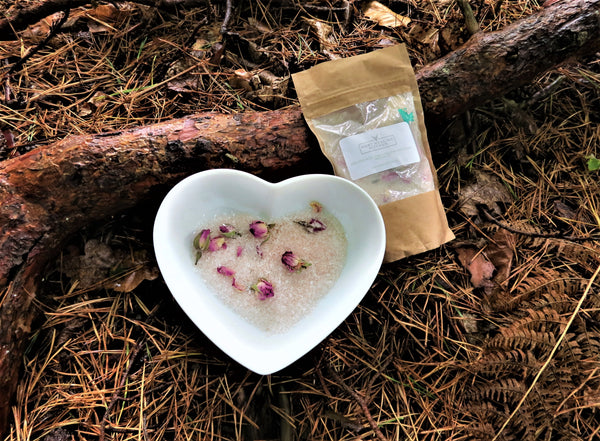 Hart Healing Kitchen bath salts with rose petals on a forest floor background