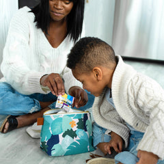 Mom and son taking out snack in diaper pouch