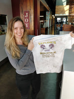 Photo of Kelly Vaughn displaying the t-shirt she received as her first payment for a freelance project