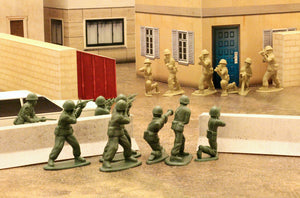 tan and green plastic army men face off in a city street made of papercraft terrain