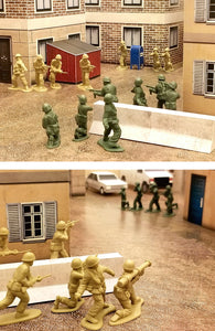 green and tan plastic army men battle it out in a papercraft terrain city complete with dumpster, mailbox and concrete barrier