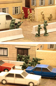 green army men face off against tan plastic army men in a city street made of papercraft terrain