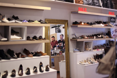 Photo shows inside of the Vegan Style boutique. It shows a mirror which reflects the image of two men, Vegan Style owners Justin Mead and Gavin Reichel. Surrounding the mirror are shelves displaying shoes