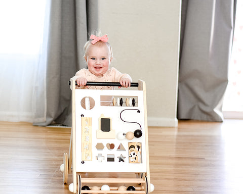 Little girl playing with eco friendly activity walker
